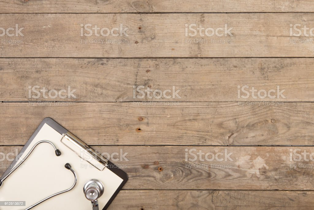 Workplace of a doctor. Stethoscope and clipboard on wooden desk stock photo