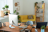 Workplace of contemporary manager or freelancer with computer monitor standing on wooden table surrounded by home environment