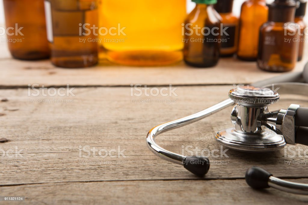 Workplace of doctor - stethoscope and pharmacy bottles on the wooden desk stock photo