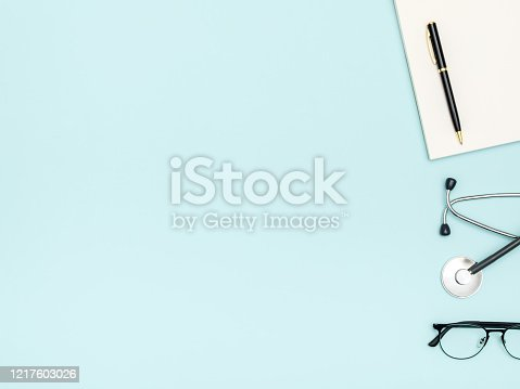 Workplace of doctor with notebook and stethoscope on colored table. Top view
