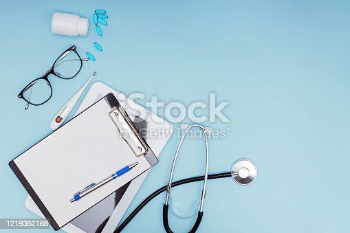 Workplace of modern doctor concept. Tablet, glasses, pills, stethoscope and other objects on blue background, top view