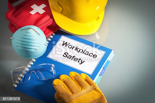 Workplace safety handbook with occupational safety equipment still life, a work training class and instruction manual for using safety equipment and administering first aid. Employment education document with protective eyewear, hard hat, first aid kit, work glove, and pollution mask. Guidance and planning tools in horizontal format with copy space.