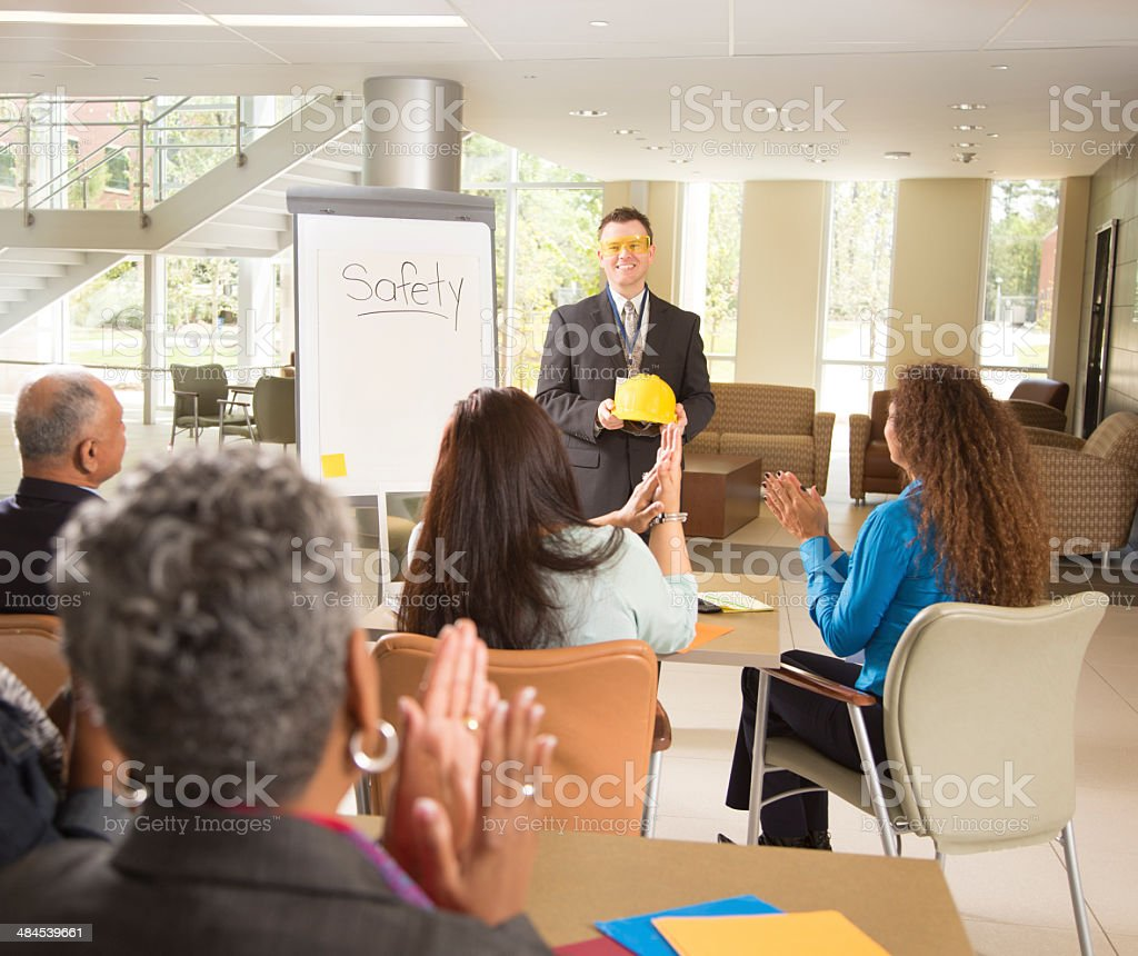 Workplace safety presentation with diverse workers stock photo