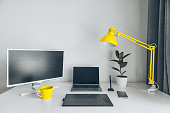 workplace. white desk with laptop and yellow cup. designer working place