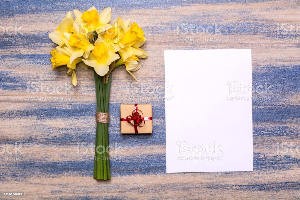 Werkplek met een cadeau met een rood lint, papier en een boeket van narcissen - Royalty-free Achtergrond - Thema Stockfoto