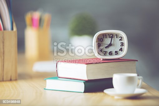 Close up of workspace with book, coffee cup, supplies and other items. Occupation, morning, leisure, knowledge and information concept