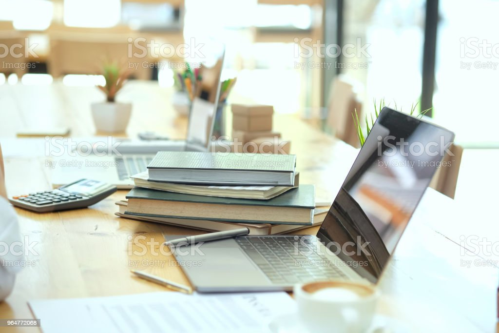 Workplace with laptop and and books on wood table with morning light. royalty-free stock photo