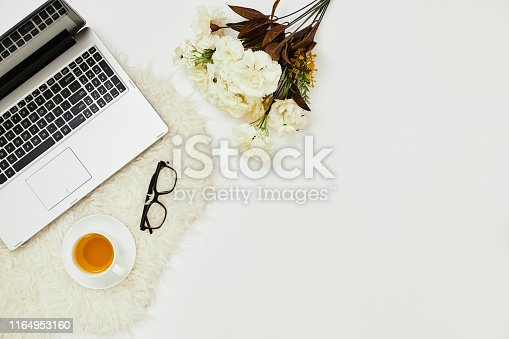 862672018 istock photo Workplace with laptop and flowers 1164953160