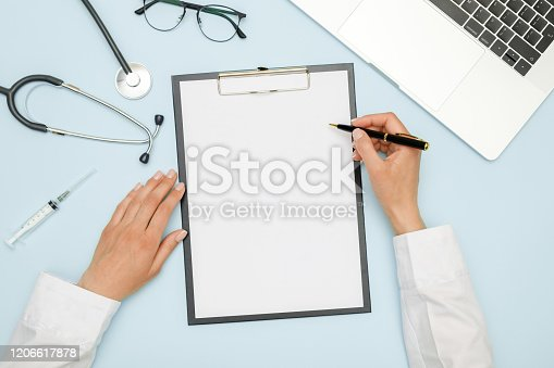 Female doctor working at workplace with laptop and medical equipment. Healthcare concept