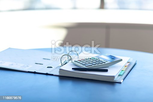 istock Workplace with notebook, pen and calculator on the desk. 1166879576