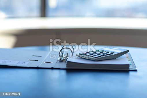 istock Workplace with notebook, pen and calculator on the desk. 1166879621