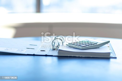 istock Workplace with notebook, pen and calculator on the desk. 1166879636