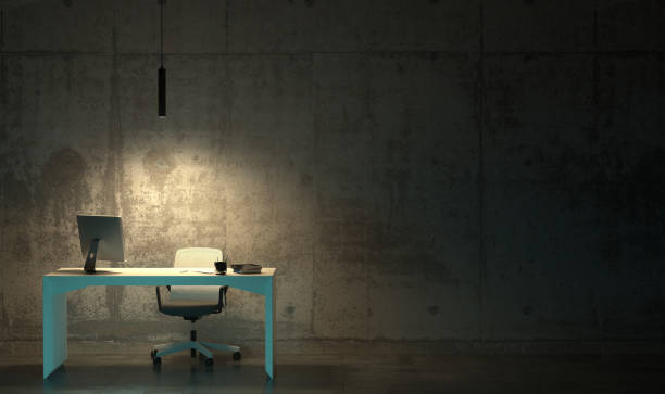 a workplace with one office desk and an armchair in an empty gloomy dark room. hard hateful work late at night in the twilight. 3d rendering of interior in loft style with copy space - concrete wall interior imagens e fotografias de stock