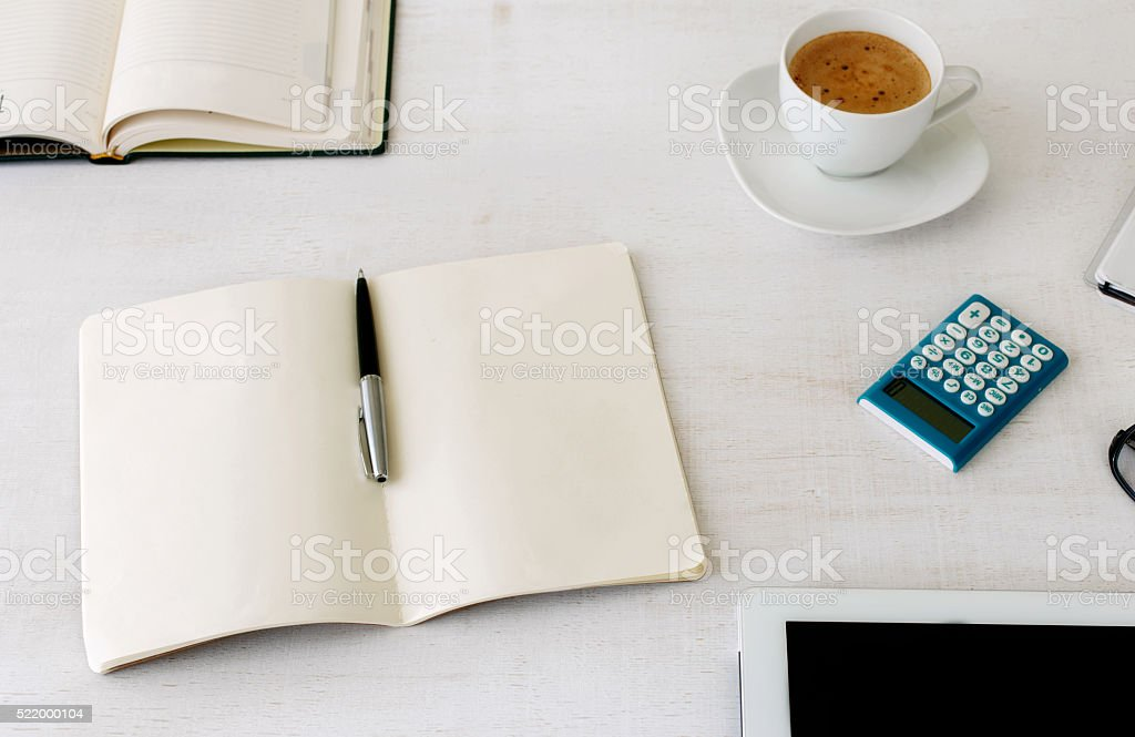 workplace with open notebook with blank pages stock photo
