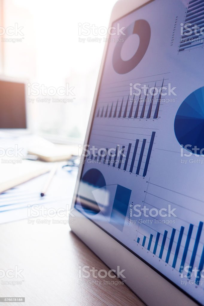 Workplace with tablet pc showing charts stock photo