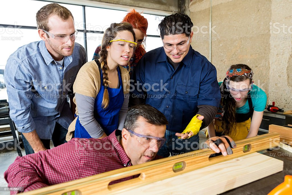 Workshop employees watch as manager uses leveler stock photo