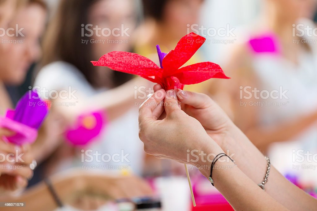 Workshop for women Group of women attending a workshop, making paper flowers. Close up of human hand holding paper flower. Adult Stock Photo