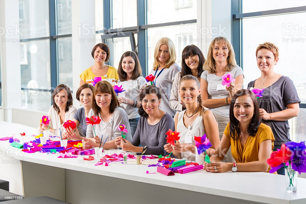 Workshop for women Portrait of group of women attending a workshop, making paper flowers, smiling at the camera. Adult Stock Photo