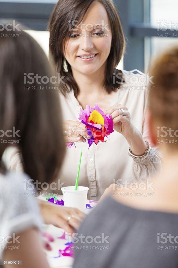 Workshop for women Women attending a workshop, making paper flowers. Focus on the smiling brunette. Adult Stock Photo