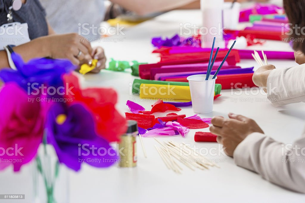 Workshop for women Group of women attending a workshop, making paper flowers. Close up of human hands and blotting paper. Adult Stock Photo