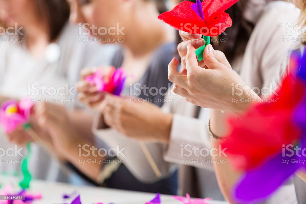Workshop for women Group of women attending a workshop, making paper flowers. Close up of human hands. Adult Stock Photo