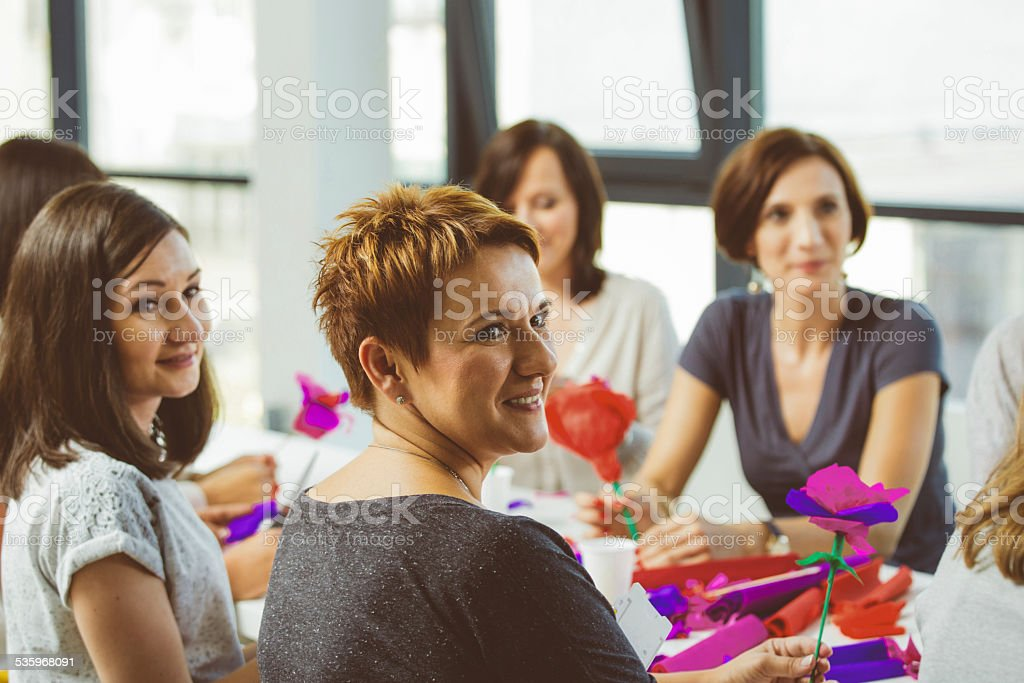 Workshop for women Group of women attending a workshop, making paper flowers. 2015 Stock Photo