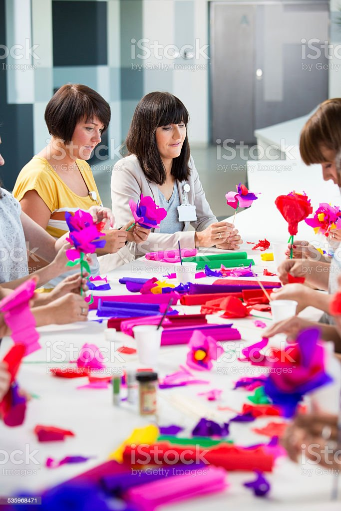 Workshop for women Group of women attending a workshop, making colorful paper flowers. 2015 Stock Photo