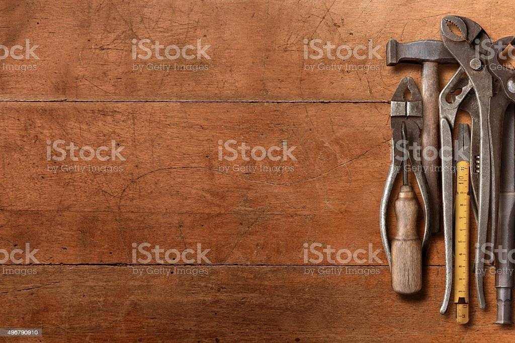 Workshop hand tools piled on a wooden desk side stock photo
