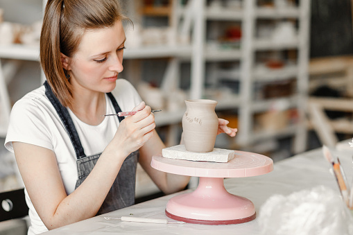 Workshop of clay pottery ceramic, woman decorating dishware pot