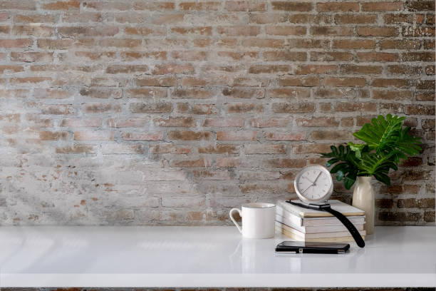 workspace desk books, house plant, pencils and clock with copy space - asian with phone house background stock photos and pictures