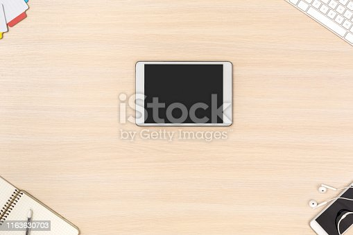 istock Workspace. Digital tablet on desk top view no people 1163630703