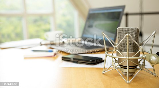 istock workspace for journalism with condenser microphone, laptop, cellphone and notepad on a desktop at the window, short panoramic banner for website headerwith blurred background, copy space 687441726