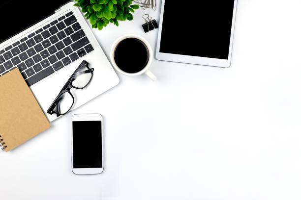 l'area di lavoro in ufficio con tablet e smartphone con schermi vuoti vuoti è in alto, vista dall'alto con spazio di copia. - flat lay foto e immagini stock