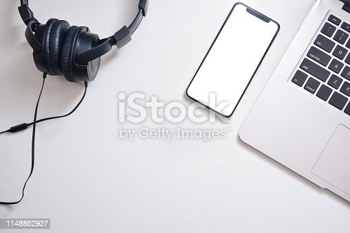 615494694 istock photo Workspace, Smartphone, headphones and laptop on a white background. Flat lay with 1148852927
