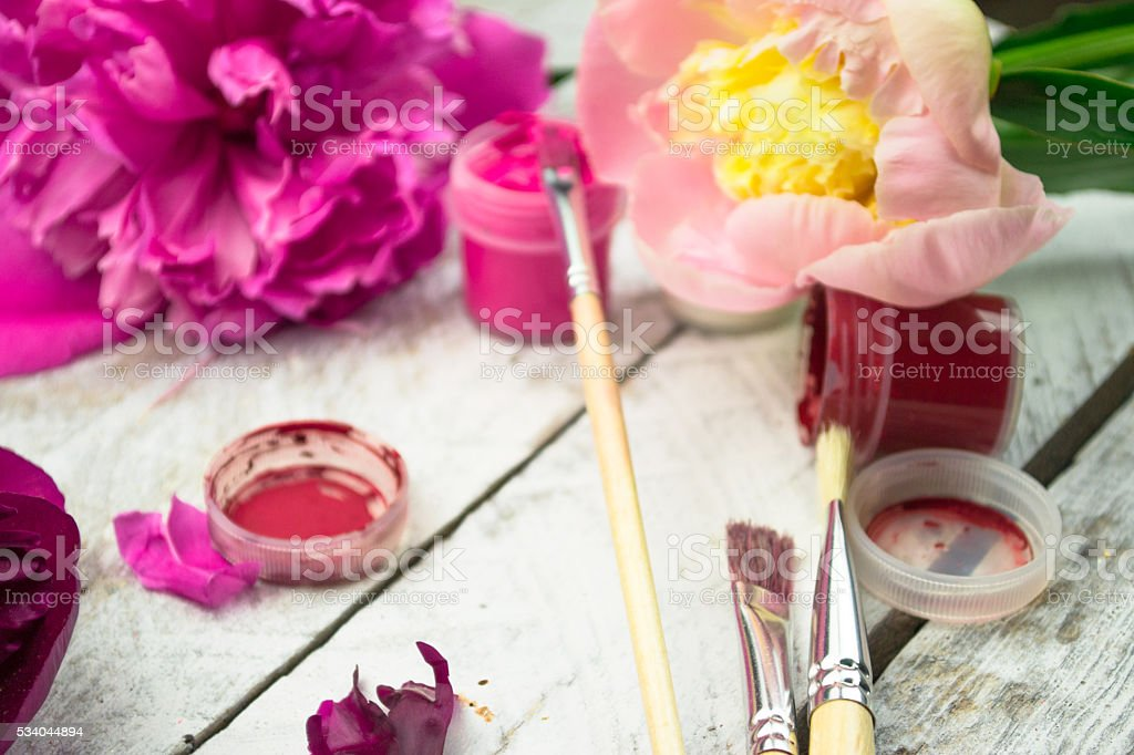 Workspace. Watercolor, paintbrush and pink peonies isolated on white background stock photo