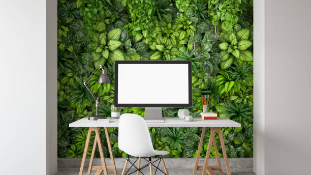 Workspace with Blank Screen Monitor and Vertical Garden Concept Wall stock photo