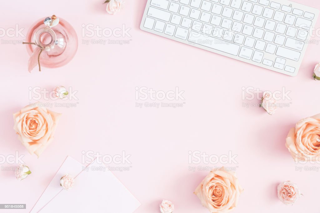 Feminine workspace with computer, rose flowers, paper blank. Flat...