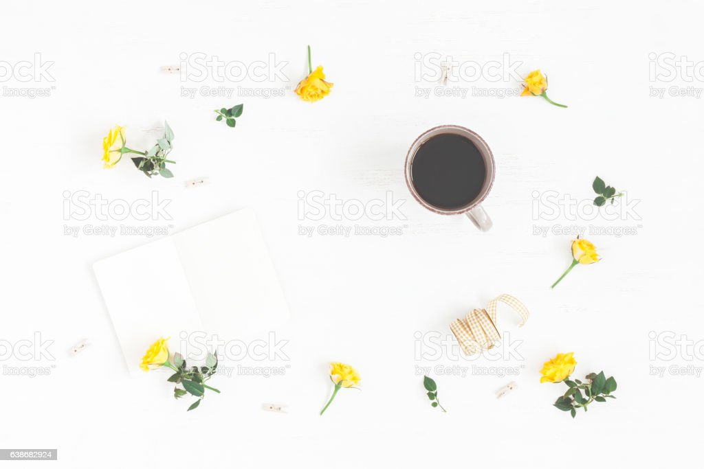 Workspace with cup of coffee, notepad, yellow flowers. Flat lay