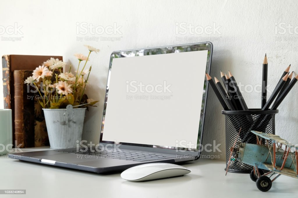 Workspace with laptop computer, office supplies plant at home or...