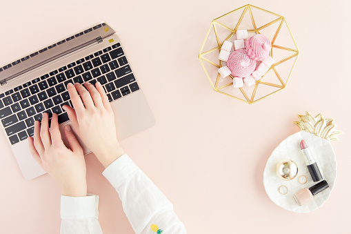Workspace with laptop, woman hands on pastel pink background. Flat lay, top view office table desk.