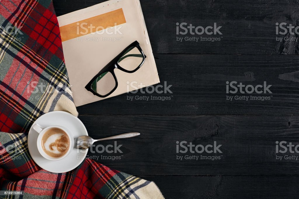 Workspace with newspaper, coffee cup, scarf, glasses. Stylish office desk. Autumn or Winter concept. Flat lay, top view stock photo