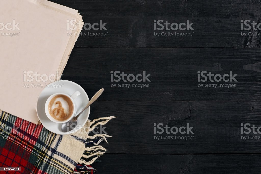 Workspace with newspaper, coffee cup, scarf. Stylish office desk. Autumn or Winter concept. Flat lay, top view stock photo