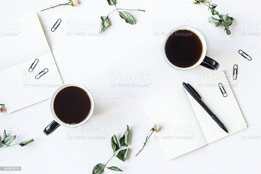 Workspace with notebook, cups of coffee and rose flowers stock photo
