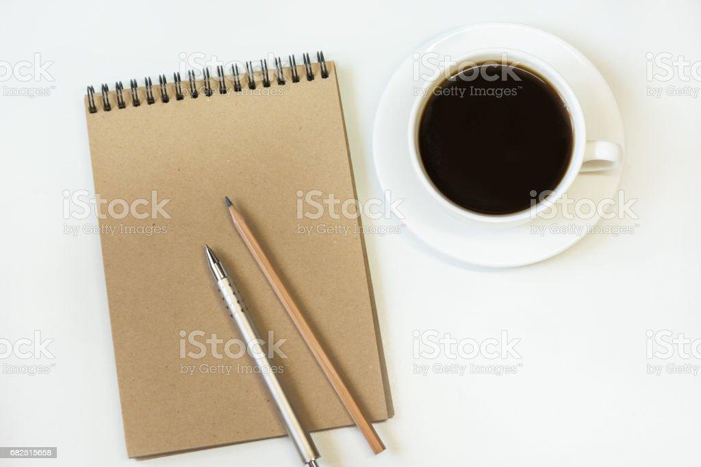 Kraft kağıt, kalem, bardak kahve beyaz zemin üzerine defter ile çalışma alanı. Görüntü metni kopya alanı ile. royalty-free stock photo