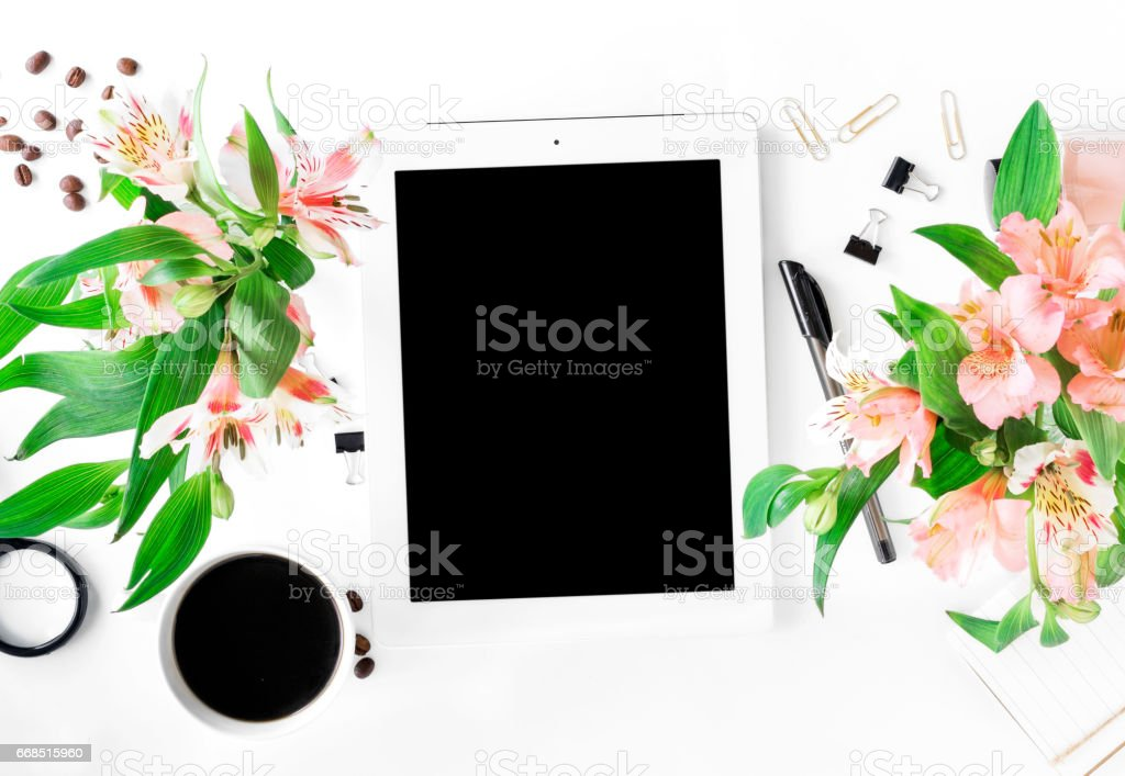 Workspace with tablet with blank screen, different office accessories, cup of coffee and bouquet of flowers. Flat lay stock photo