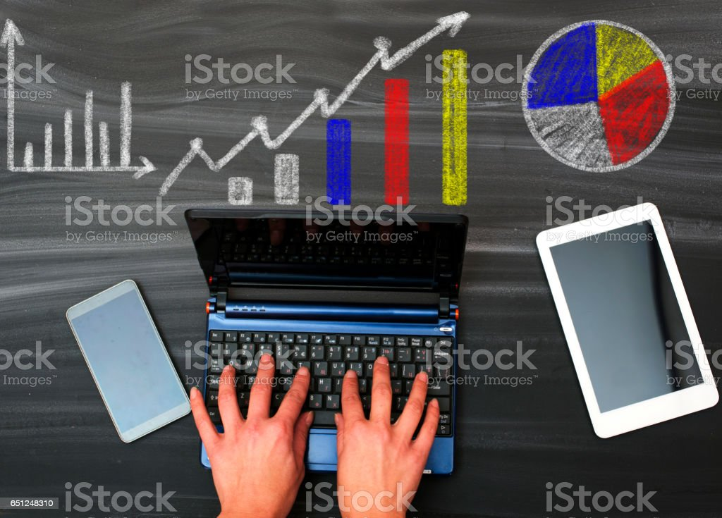 Workspace with various charts on chalkboard stock photo