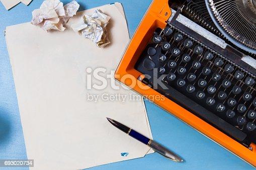 istock Workspace with vintage orange typewriter 693020734