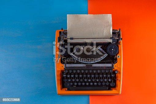 istock Workspace with vintage orange typewriter 693020868