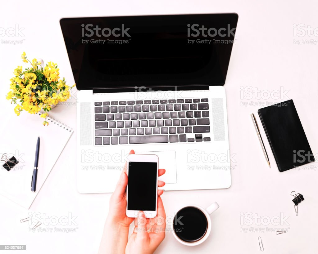 Workspace with woman hand holding phone at laptop yellow flowers