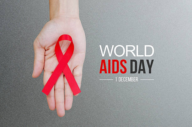 World Aids Day concept. Female hands holding red ribbon HIV, AIDS awareness ribbon. World Aids Day concept. aids stock pictures, royalty-free photos & images
